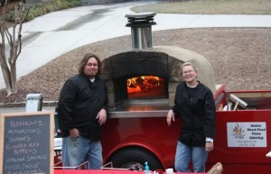 Jonathan and Sarah standing in front of their woodfired oven